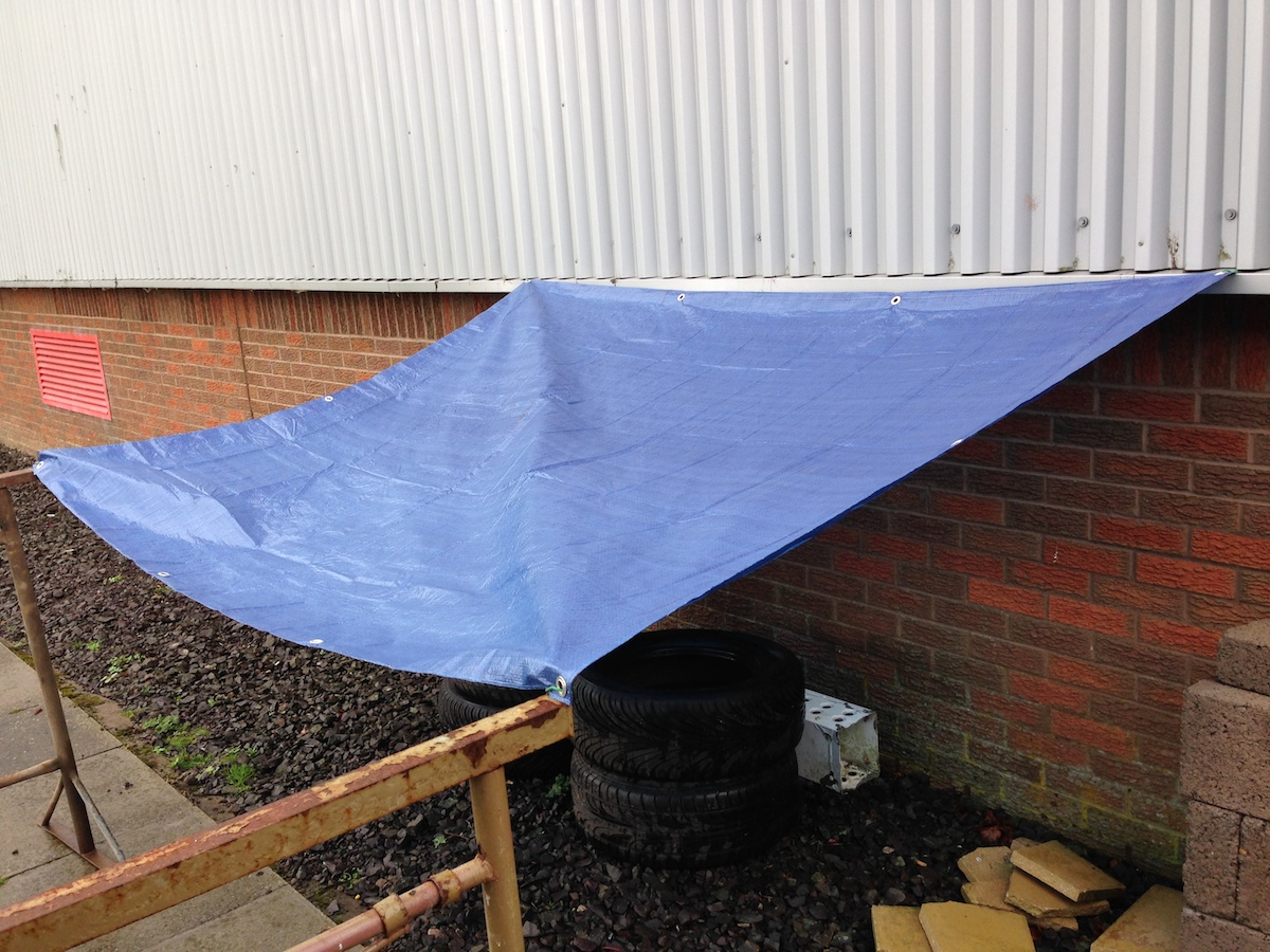 A green tarpaulin covering a skip by Yuzet.