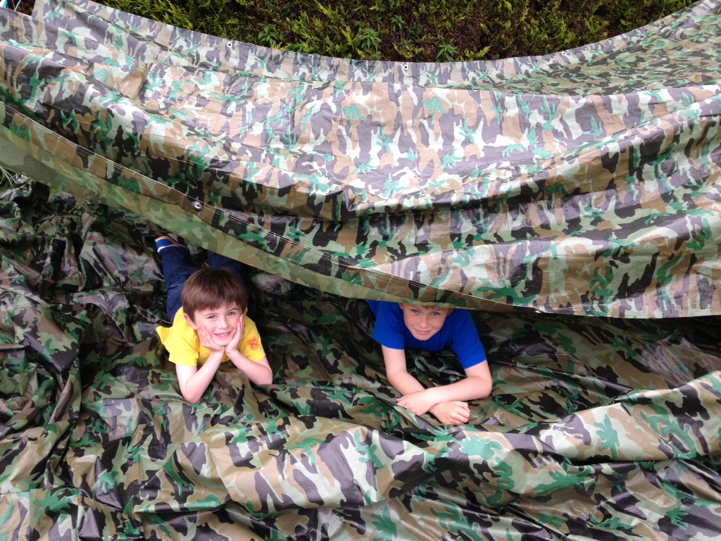 Two boys using a camouflage tarpaulin as a play shelter by Yuzet®.